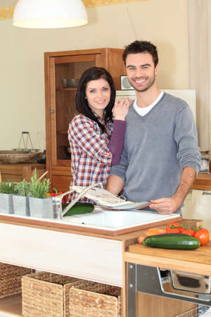 Smiling woman and man in kitchen photo