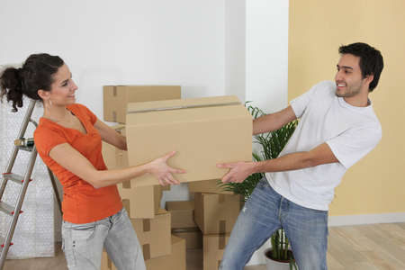 unpacking: Couple carrying moving boxes