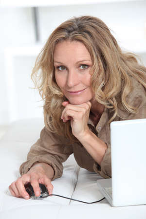 Smiling relaxed woman with laptop computer photo
