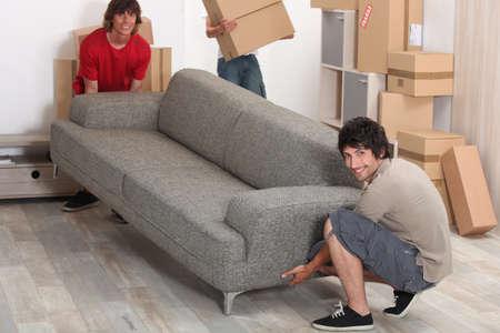 levantamiento: foto de los amigos de mover un sof� Foto de archivo