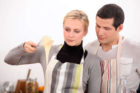 Young man and young woman making a cake dough photo