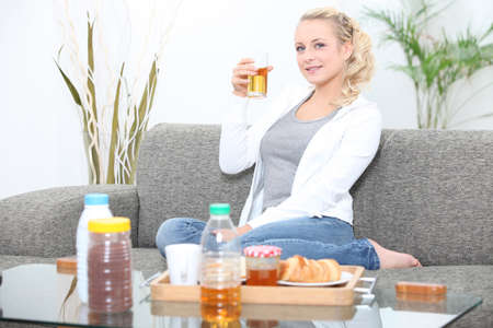 Woman having breakfast in her living room Stock Photo - 11132560