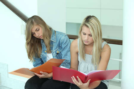 comments: Two female students looking through work folders Stock Photo