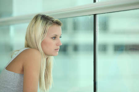 Blond female teenager sat looking out of window photo