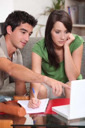 hombre escribiendo: pareja que busca en la computadora port�til y tomar notas
