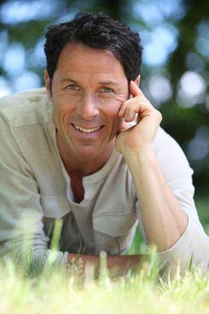 man 40 50: Man smiling lying on the grass.