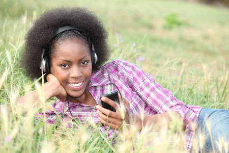 Une femme noire écouter de la musique tout en jetant sur l'herbe. Banque d'images