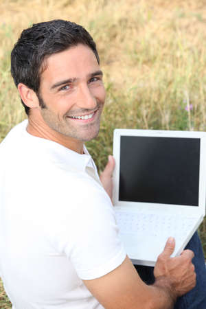 Smiling man using a laptop with a blank screen in a field photo