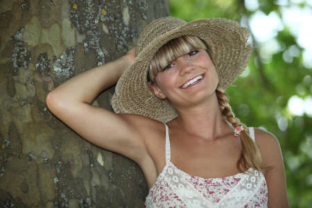 plait: Summery woman standing by a tree Stock Photo