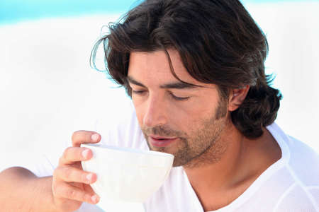 silently: Man drinking coffee by swimming pool
