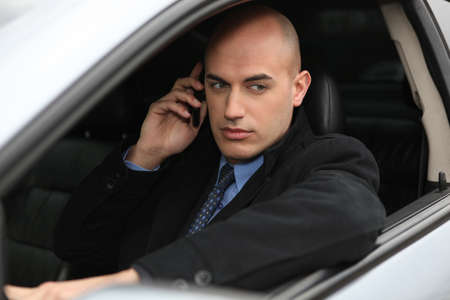 Businessman using a phone in his car photo