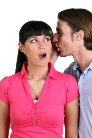 blab: Young man whispering a secret into a woman