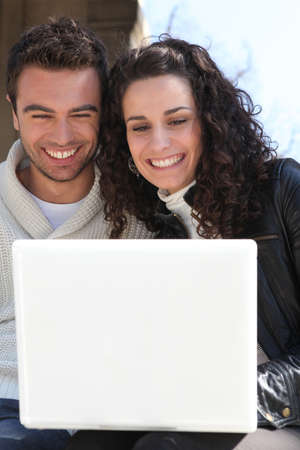 season photos: Couple outdoors with laptop Stock Photo