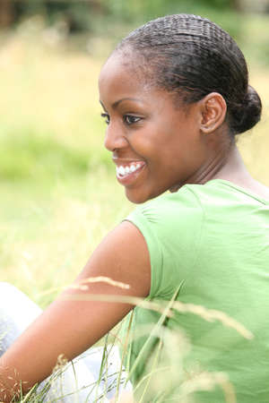 ebony: African woman sitting in the grass Stock Photo