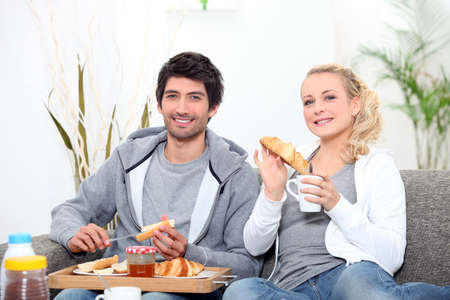 Young couple sharing breakfast in the lounge photo