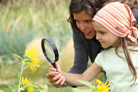 Mother and daughter looking at a flower with a magnifying glass photo
