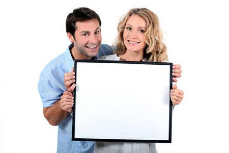 Couple holding white board photo