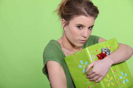 selfish: Greedy woman hugging her present all to herself Stock Photo