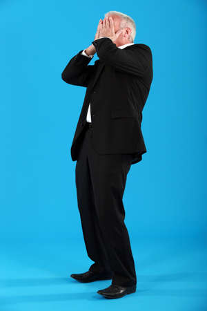 Well-dressed man covering his face with his hands photo