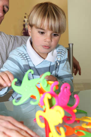 Little boy playing with a colourful toy photo