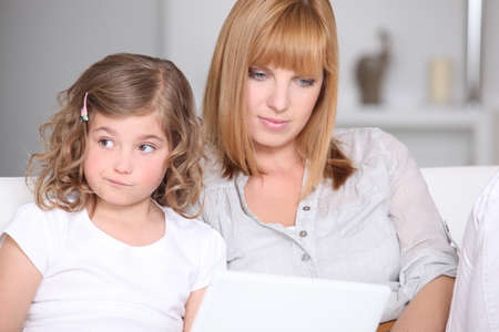 Unimpressed little girl with her mother and a laptop photo