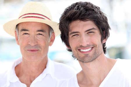 convivialit�: 65 ann�es vieil homme portant un chapeau de paille et une 25 ann�es vieil homme posant dans une atmosph�re de vacances d'�t�