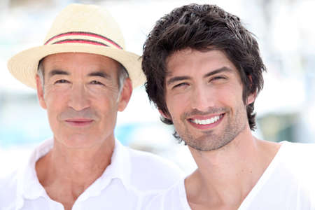 friendliness: 65 years old man wearing a straw hat and a 25 years old man posing in a summer vacation atmosphere Stock Photo