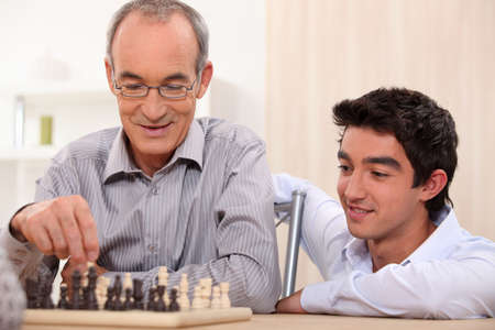 intergenerational: a senior man playing chess Stock Photo