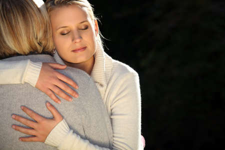 two parents: A mother and her teenage daughter hugging.