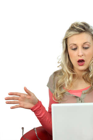 Girl with expression of surprise using laptop computer photo