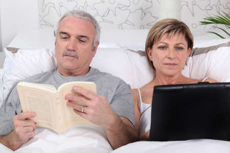 net book: Man reading in bed while his wife surfs the internet