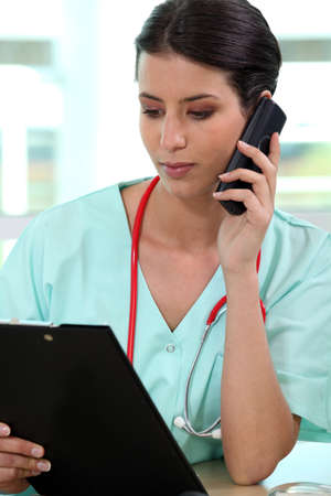 Female medic making a telephone call Stock Photo - 11132291