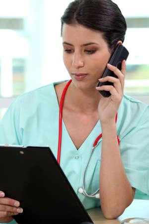 pielęgniarki: Kobieta medyk nawiązywania połączenia telefonicznego