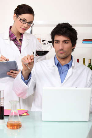 experimenter: Man and woman testing wine in laboratory