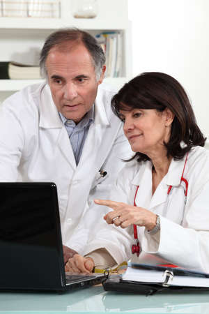 healthcare workers: Doctors looking at a computer and sharing their opinions Stock Photo