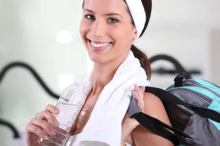 excretion: Woman with bag leaving gym