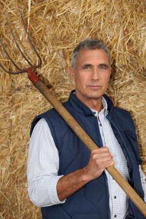 men 45 years: Farmer holding a pitchfork Stock Photo