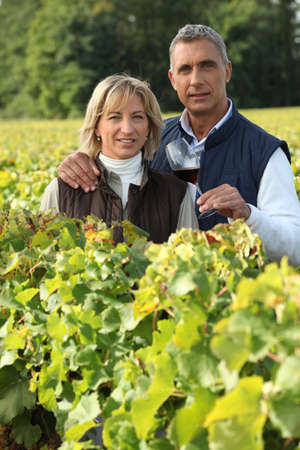 couple in the vines, man holding a red wine glass photo