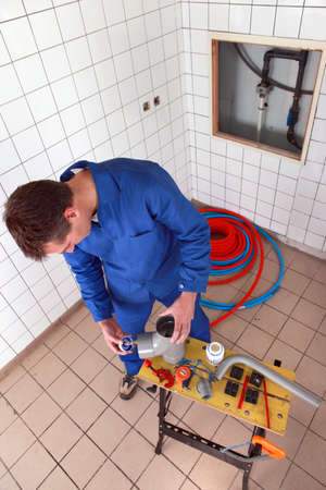 Plumber fixing two parts together photo