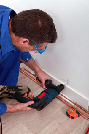 Plumber drilling a wall photo