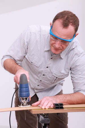 whittle: Carpenter with goggles using drill
