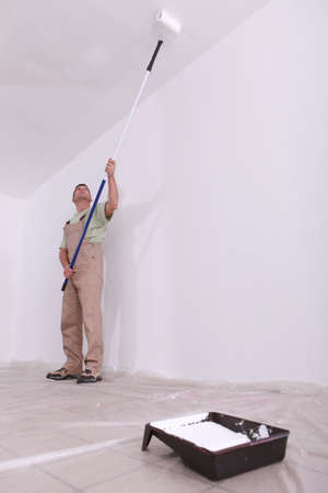 house painter: craftsman painting a ceiling Stock Photo