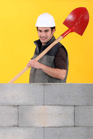 Worker stood by wall with spade Stock Photo - 11136302