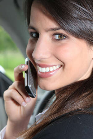 Smiling brunette on a mobile in a car photo