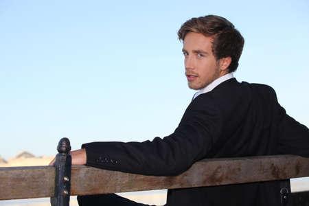 při pohledu na fotoaparát: Mladý muž při odpočinku na lavičce Reklamní fotografie