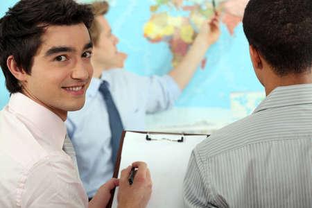 negocios internacionales: Joven empresario de discutir un mapa Foto de archivo