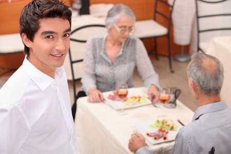 mature couple and young waiter at restaurant photo