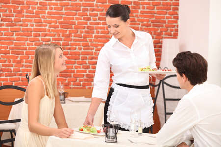 side order: couple interacting with waitress at a dinner Stock Photo