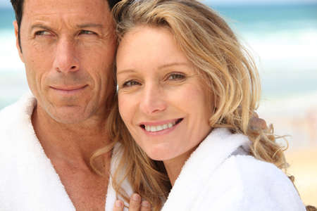 Closeup of a couple on the beach in toweling robes photo