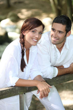 natural love: Couple in white leaning on a wooden fence